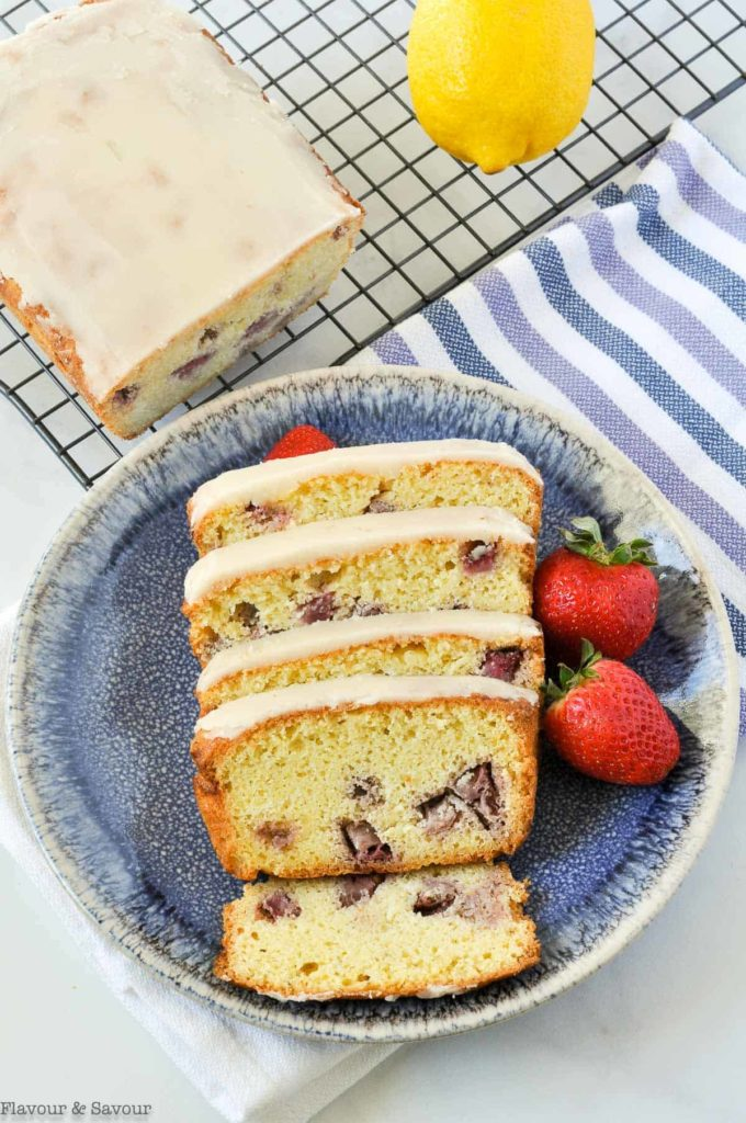 Overhead view of Strawberry Lemon Loaf on a rack with slices on a blue plate