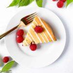 A slice of flourless Raspberry Lemon Ricotta Cake with fresh raspberries and raspberry leaves