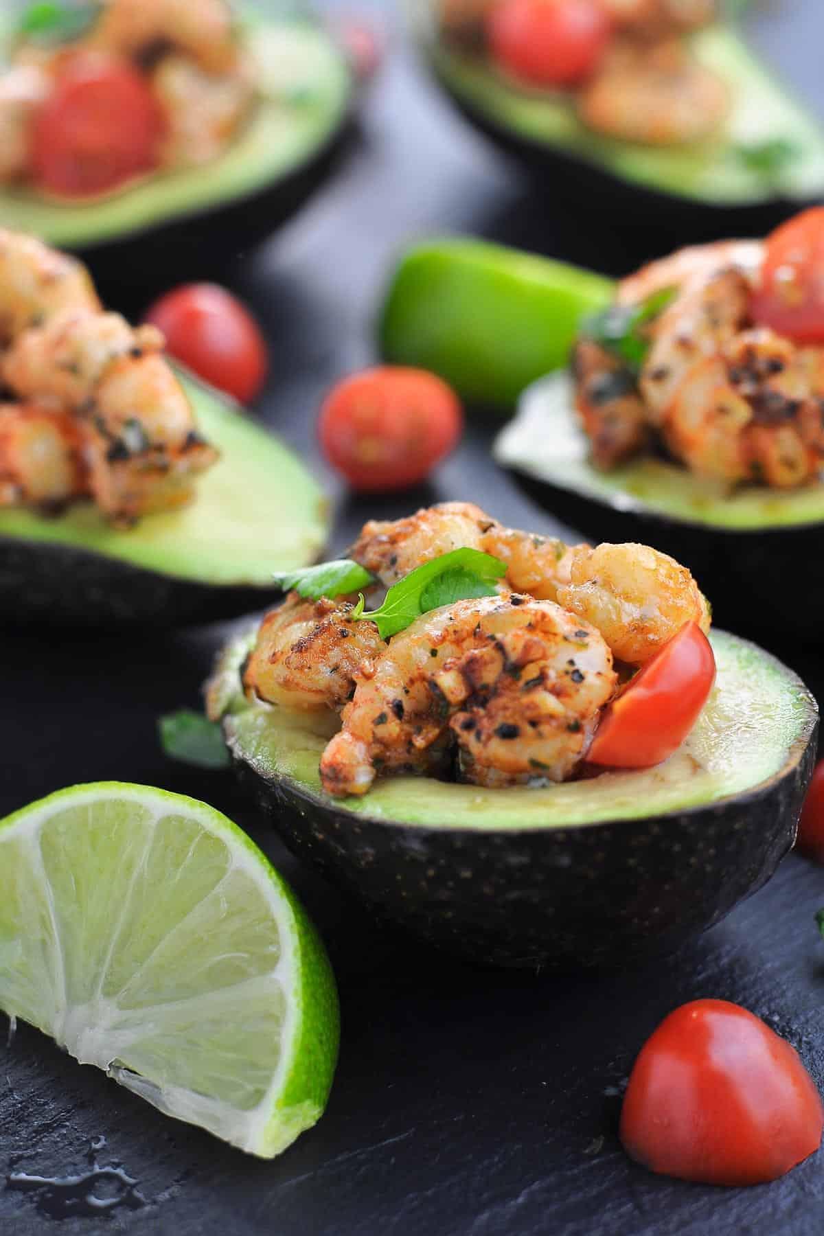 Cajun Shrimp Stuffed Avocados with quartered limes on a black tray