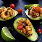 Cajun Shrimp Stuffed Avocados overhead view with cherry tomatoes and limes