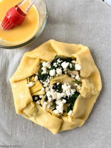 Brushing egg wash on spinach artichoke galette