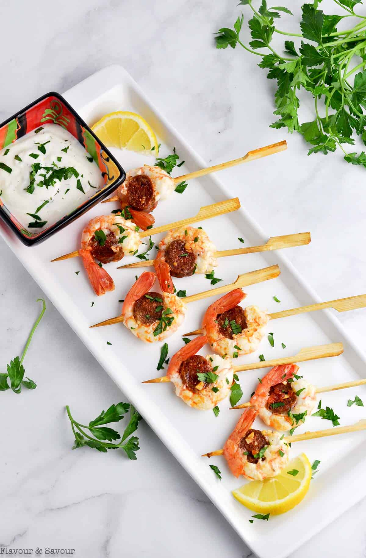 8 Prawn and Chorizo Skewer appetizers with a small dish of lemon dipping sauce