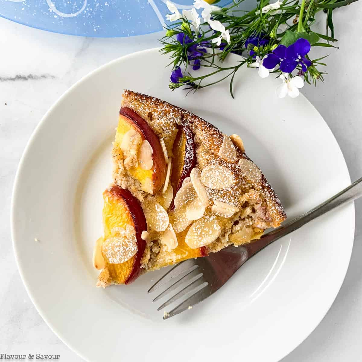 A slice of Gluten-Free Flourless Nectarine Ricotta Cake on a white plate with fresh blue and white flowers