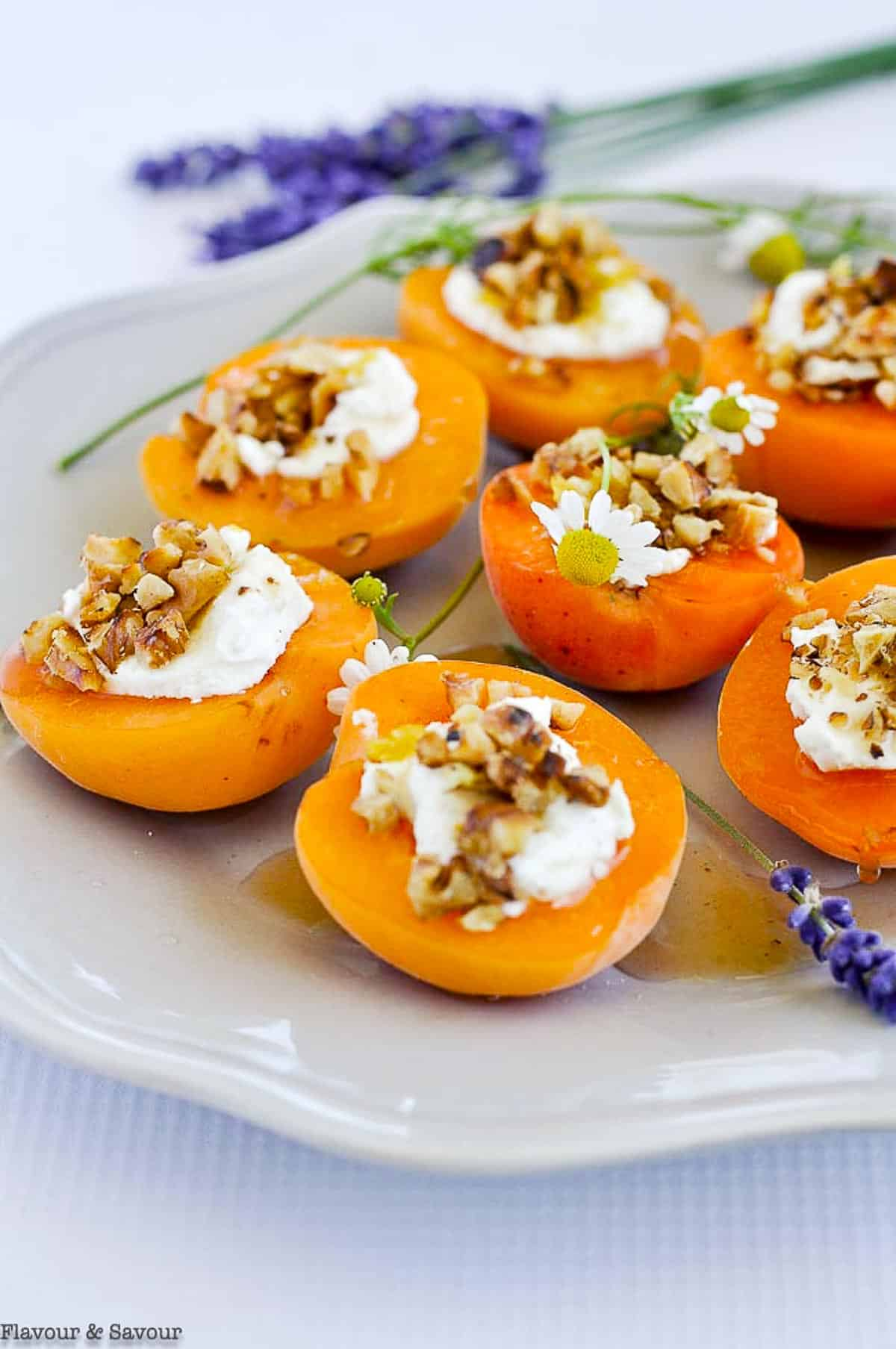 A plate with several fresh apricots topped with goat cheese and lavender honey