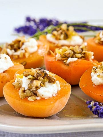 Fresh apricots on a gray plate topped with goat cheese, walnuts and honey with lavender sprigs