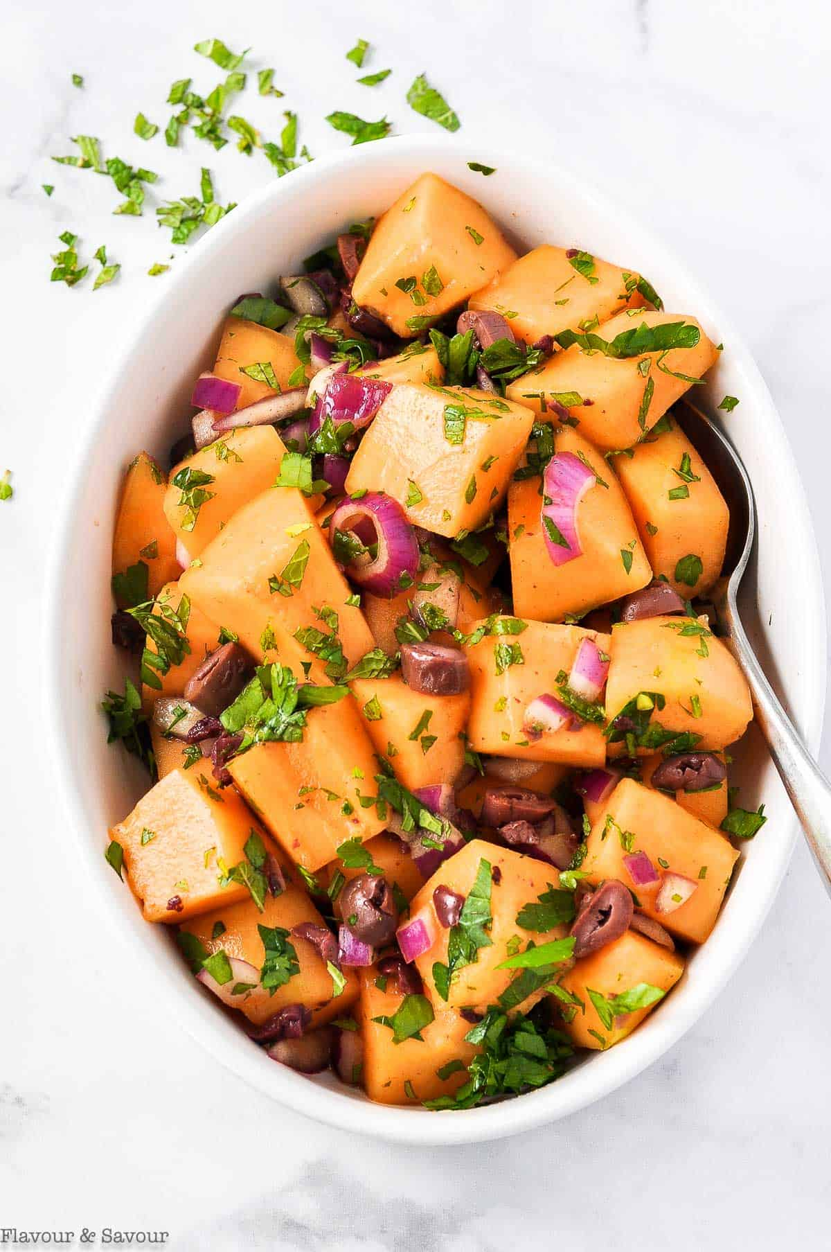 Overhead view of Mediterranean Cantaloupe Salad with olives, red onion, chopped parsley and mint leaves.