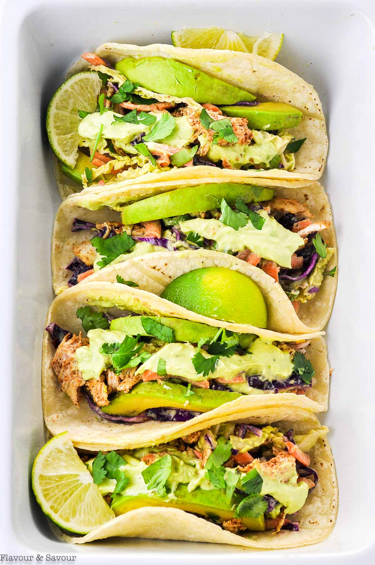 Four Shredded Chicken Tacos in a white serving dish