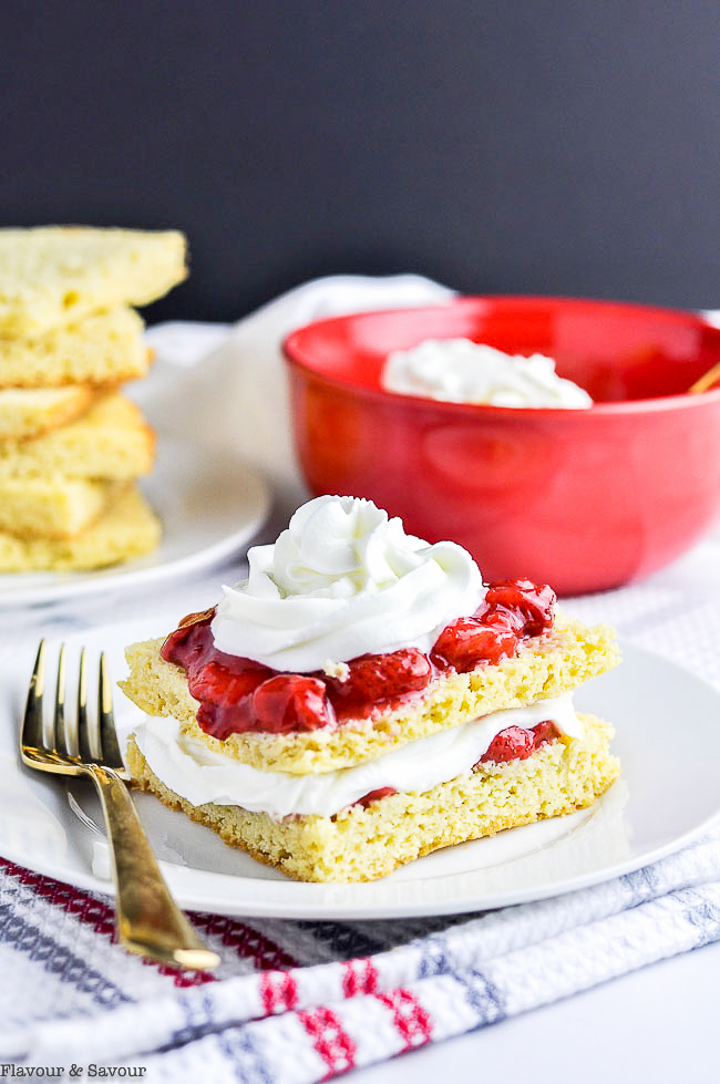 Sugar-Free Strawberry Shortcake topped with a red bowl of whipped cream in the background.