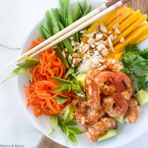 Overhead view of Vietnamese Prawn (Shrimp) Noodle Bowl with snow peas, carrots, mango, avocado and fresh herbs