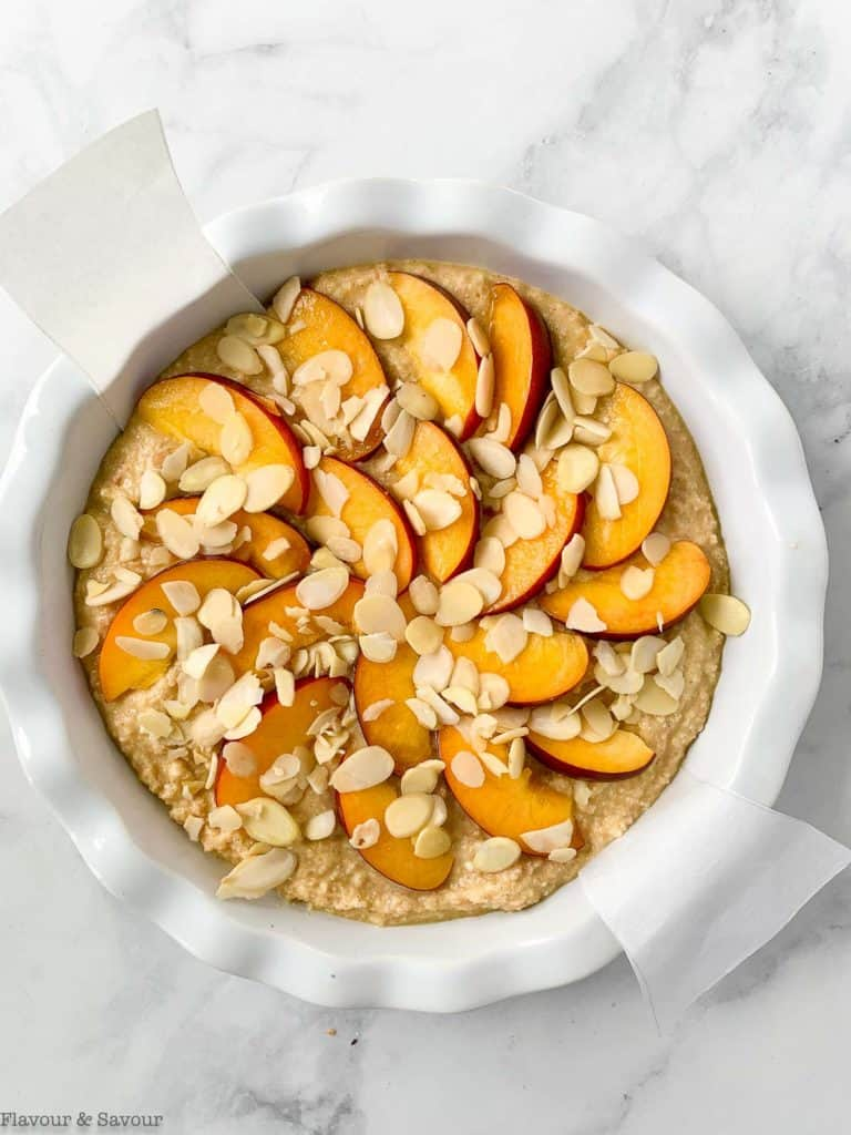 Arranging nectarine slices and almonds on top of cake