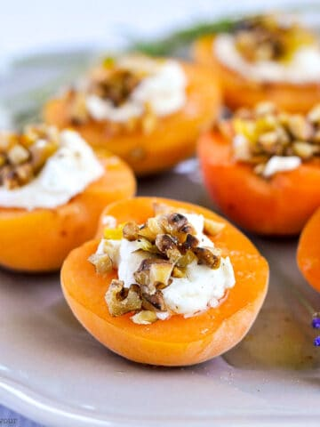 a plate with fresh apricots topped with goat cheese, walnuts and honey