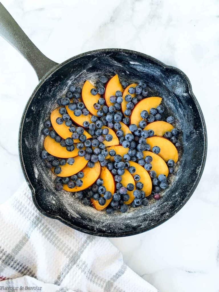 Peaches and blueberries arranged in a cast iron skillet