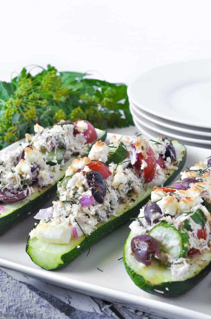 Baked Stuffed Zucchini Boats with Chicken and Feta on a serving plate with fresh herbs