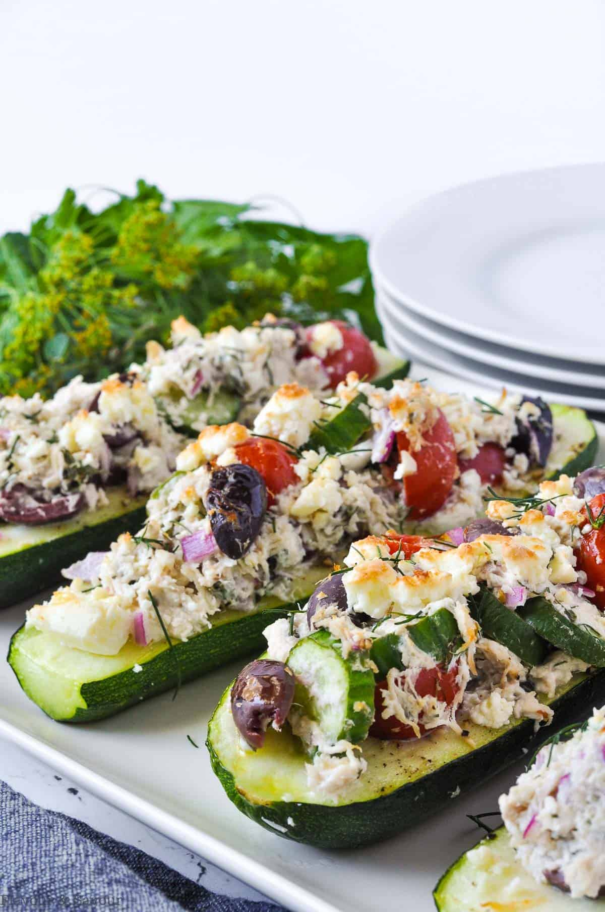 Greek Chicken Stuffed Zucchini Boats with herbs and plates in the background