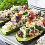 close up view of Greek Chicken Stuffed Zucchini Boats with plates in the background