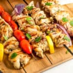 Greek Lemon Chicken Kabobs on a cutting board with lemon slices