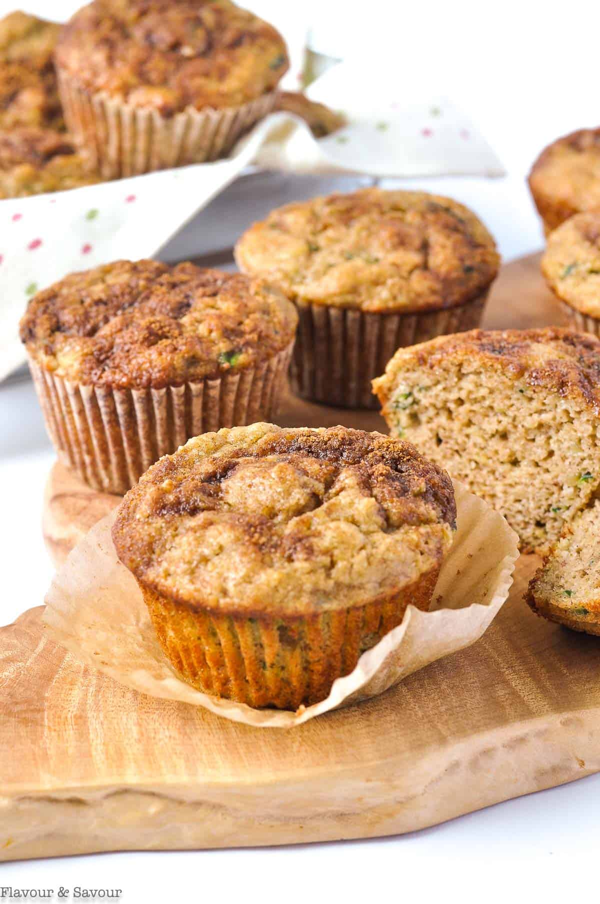 Zucchini Banana Muffins on a board with a basket of muffins in the background
