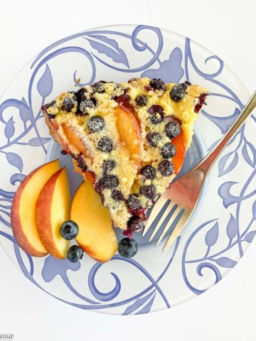 A slice of Gluten-Free Blueberry Peach Clafoutis on a blue patterned plate with fresh peach slices