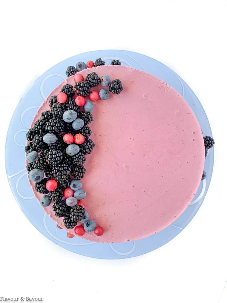 Beginning to decorate Blackberry Cheesecake Ice Cream Cake with fresh blueberries and blackberries.