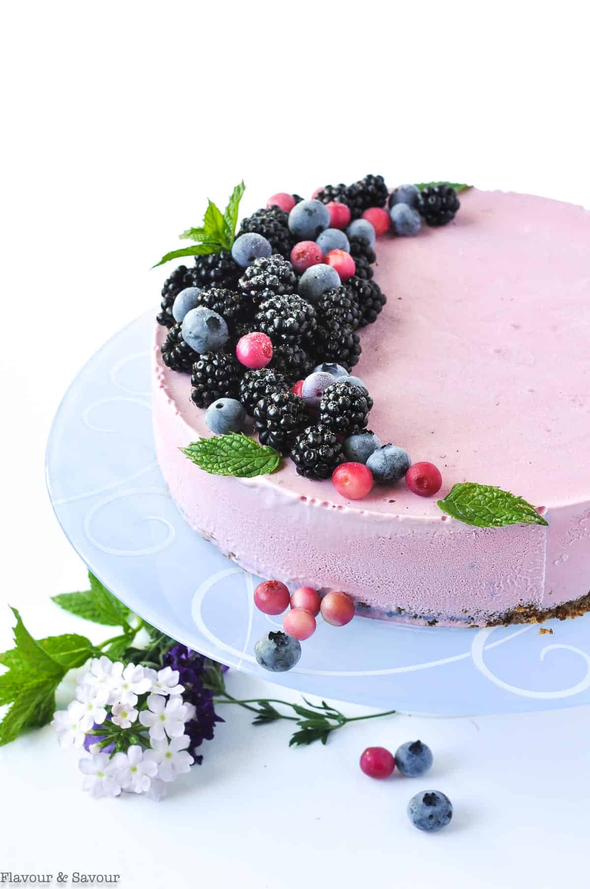 Blackberry Ice Cream Cheesecake decorated with berries on a pale blue plate.