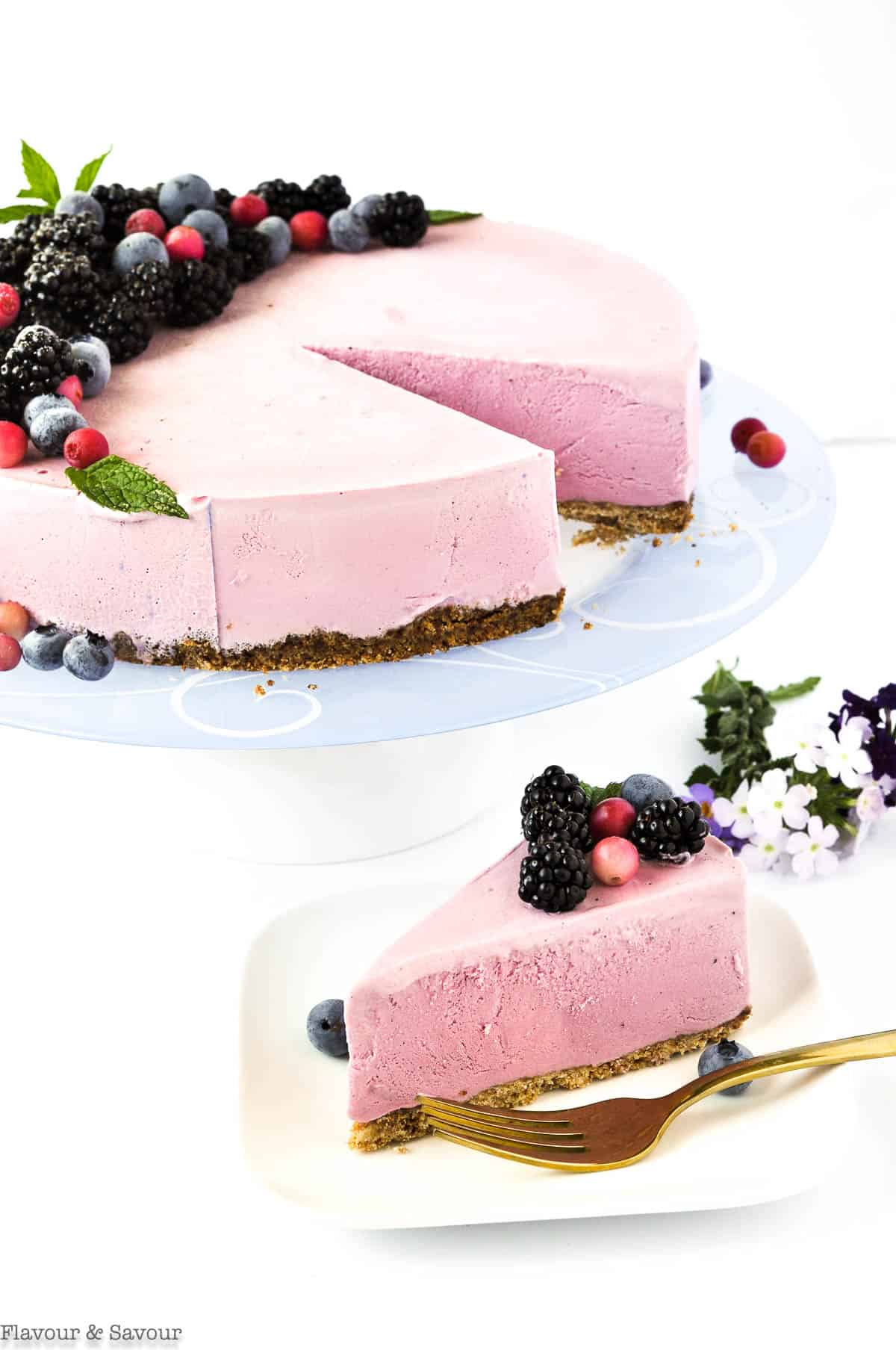 Blackberry Ice Cream Cheesecakeon a pedestal stand with a slice on a plate with a fork