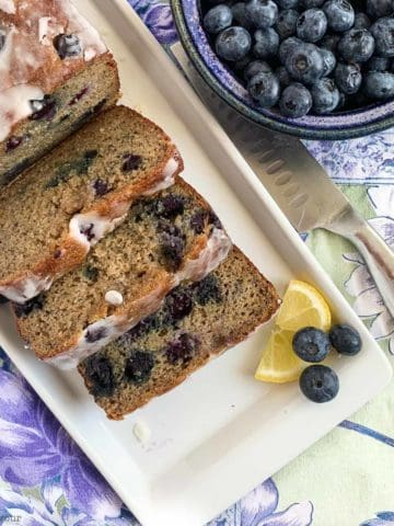 Grain-Free Blueberry Banana Bread sliced next to a bowl of fresh blueberries