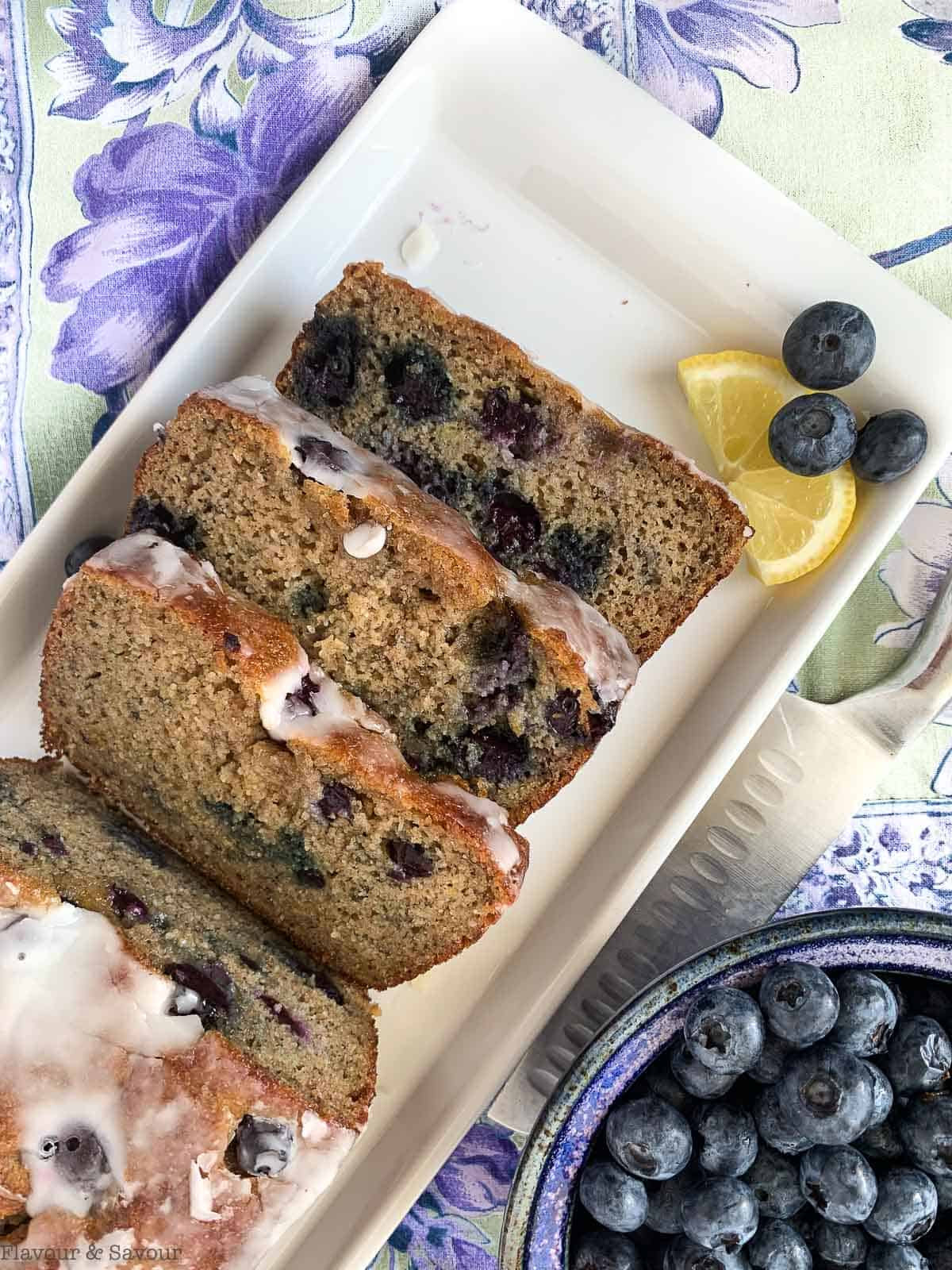 Slices of Blueberry Banana Bread on a white plate with a bowl of blueberries nearby.