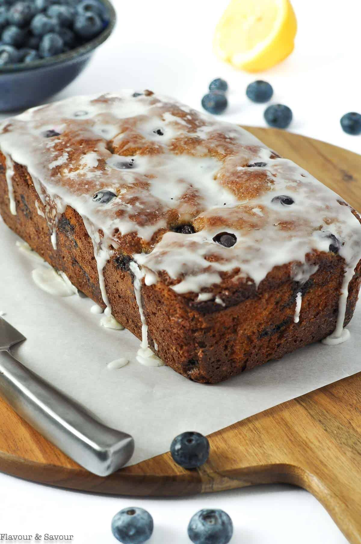 A loaf of blueberry banana bread with lemon glaze drips