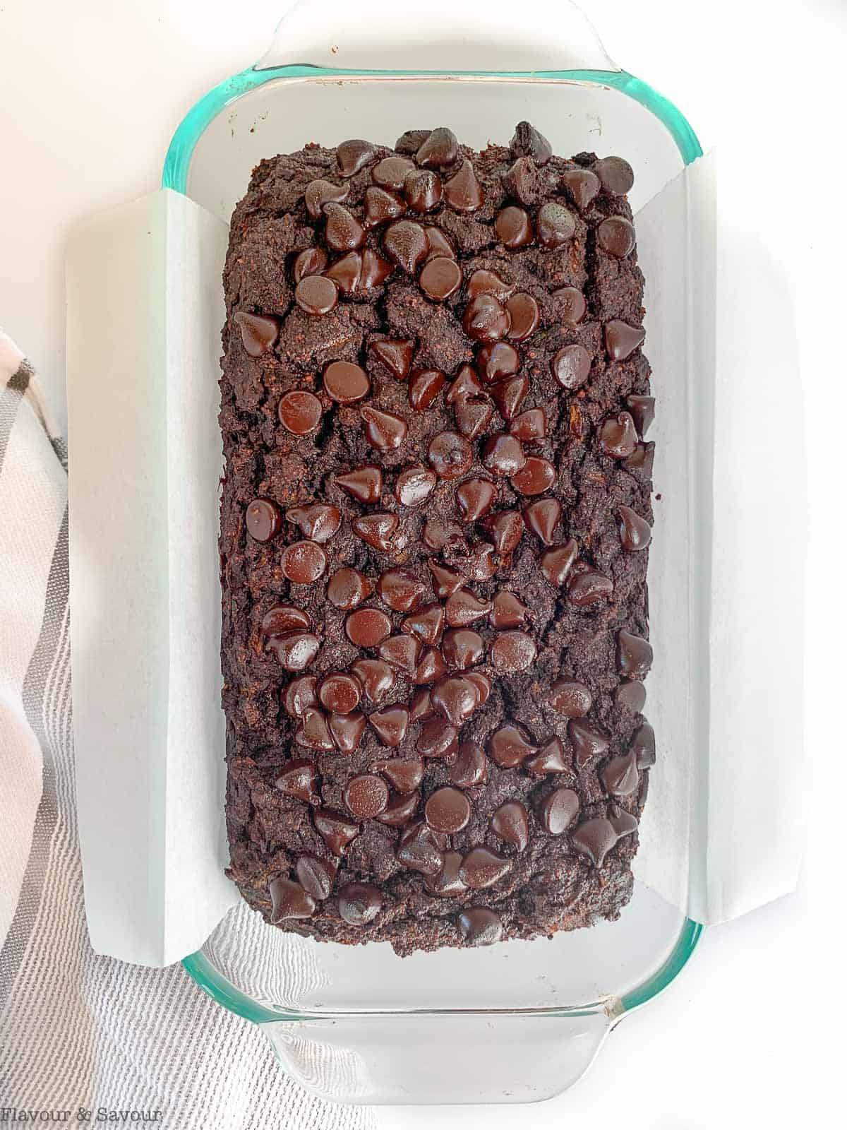 Double Chocolate Zucchini Bread in a loaf pan lined with parchment paper