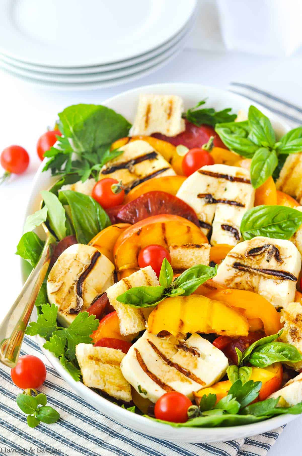 Grilled Halloumi Peach and Tomato Salad in a serving bowl with a stack of white plates