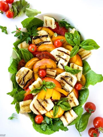 Overhead square image of grilled Halloumi Peach and Tomato Salad on a white background