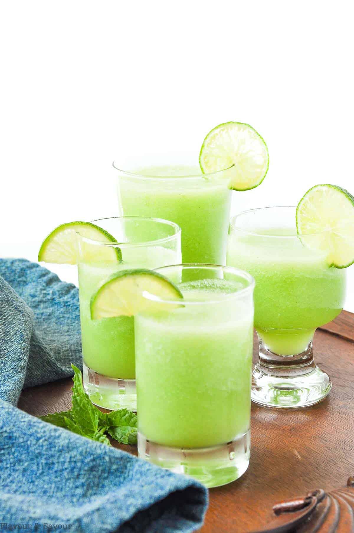 Four glasses of Honeydew Lime mocktail garnished with lime slices