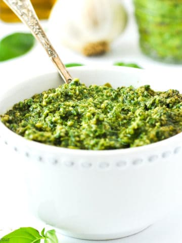 a small bowl of basil cashew pesto with a spoon