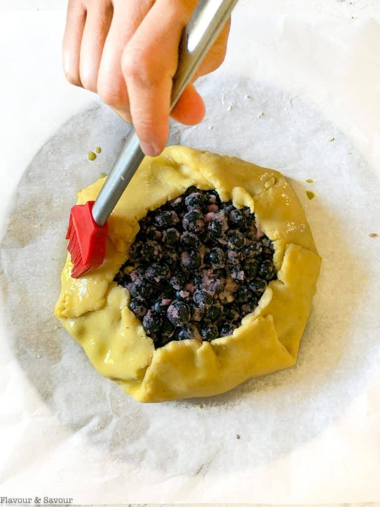 brushing egg wash on galette pastry for blueberry lemon galette