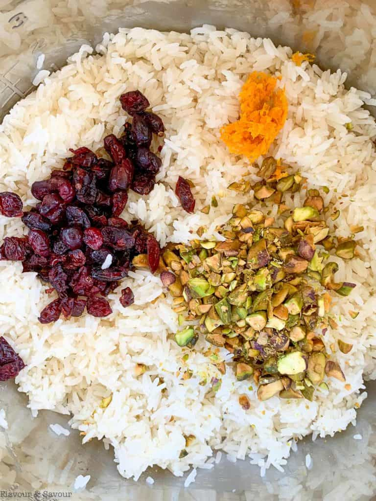 Adding cranberries, pistachio and orange zest to cooked rice