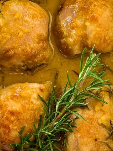 Easy Baked Maple Dijon Chicken in baking dish with a sprig of rosemary