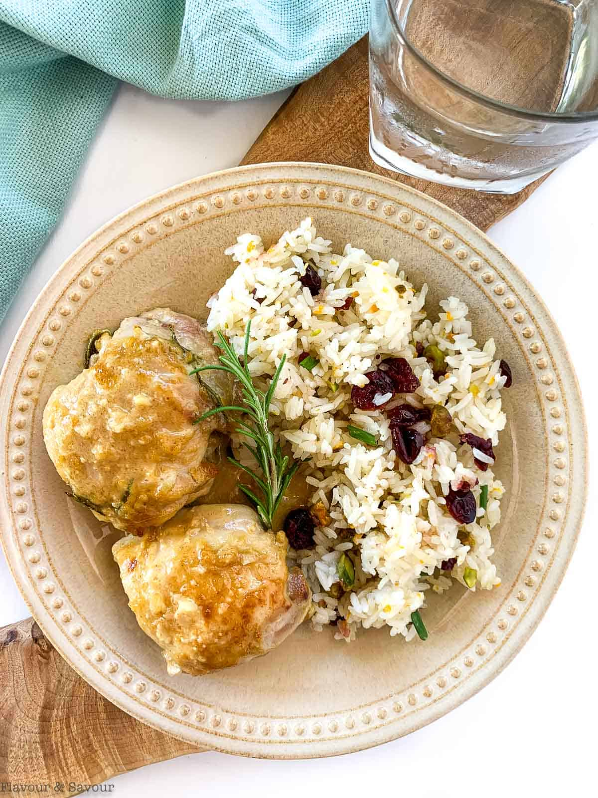 Two Maple Dijon Chicken Thighs on a plate with Cranberry Jasmine Rice