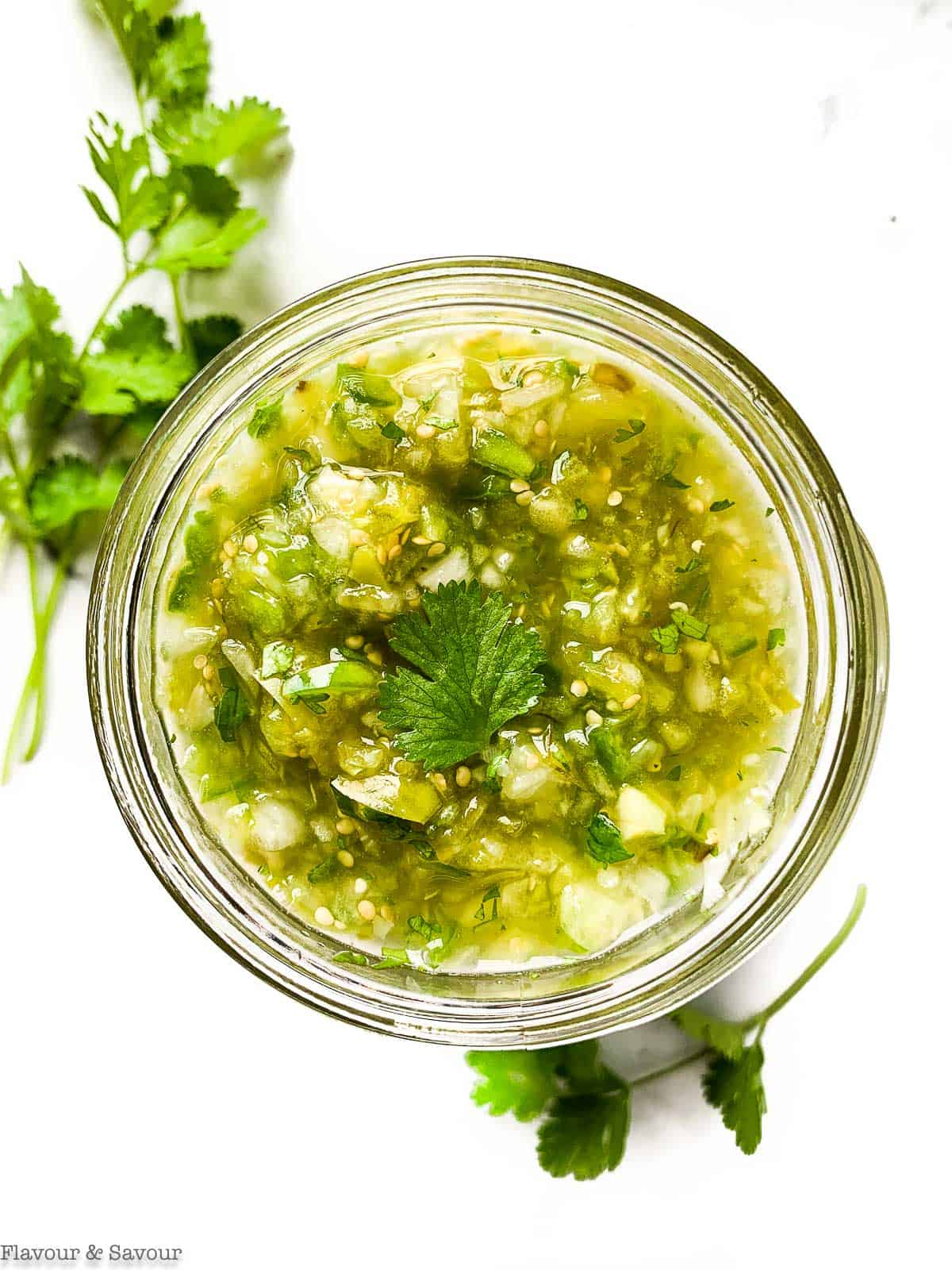 Roasted Tomatillo Salsa Verde in a Mason Jar with cilantro sprigs beside.