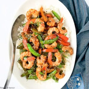 Overhead view of Shrimp and Snow Pea Stir Fry in a white serving bowl with a spoon