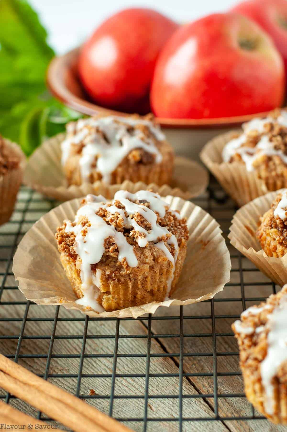 Glazed Apple Muffins with a bowl of apples in the background