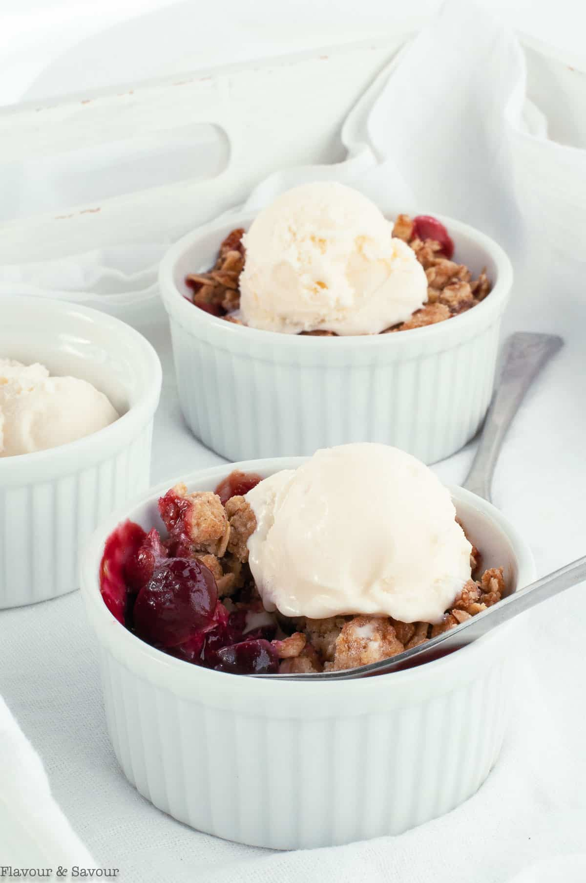 A spoonful of Air Fryer Cherry Almond Crisp with ice cream