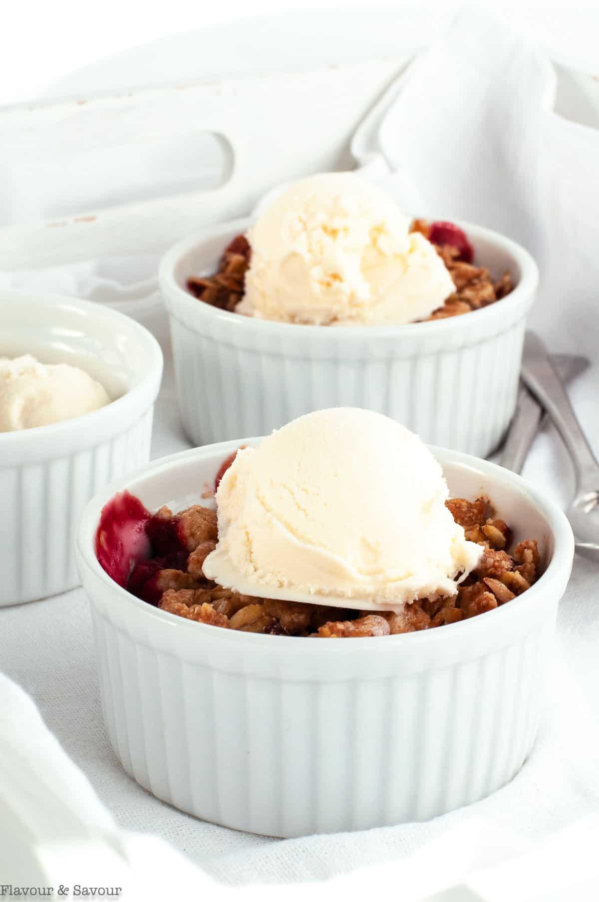 Two ramekins with mini Cherry Almond Crisp with ice cream