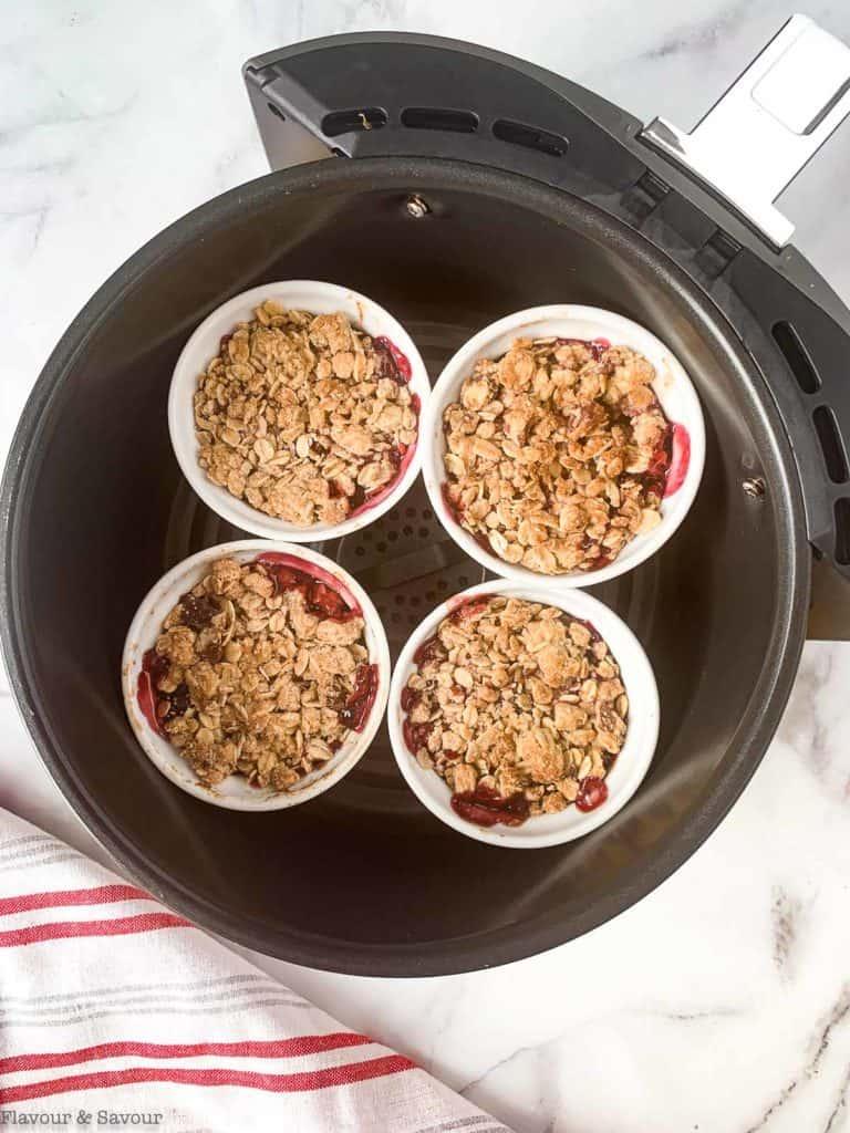 Four ramekins with cherry crisp in an air fryer basket