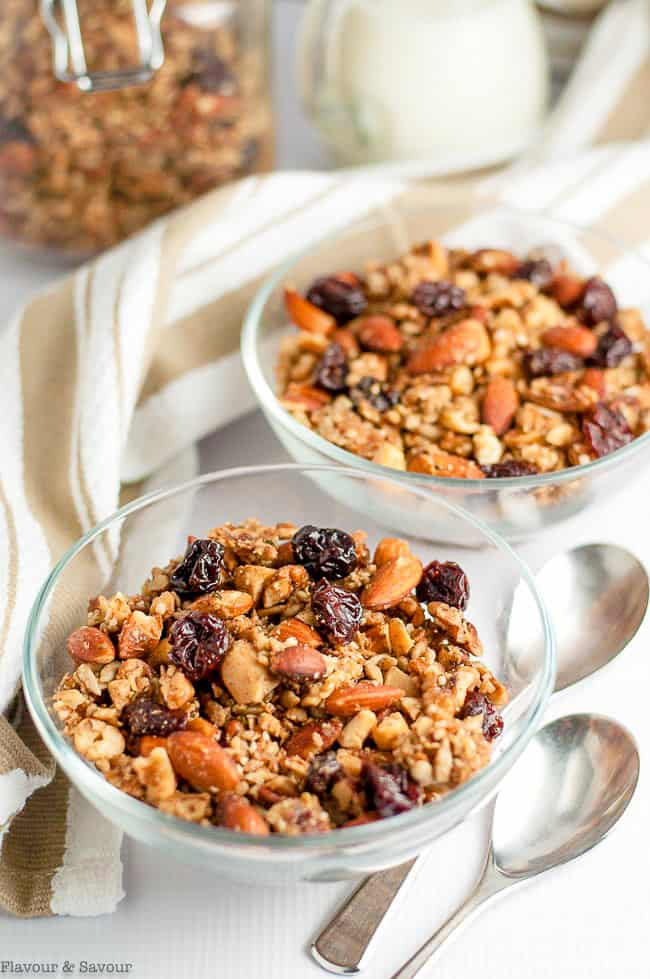Overhead view of two bowls of grain-free granola with a glass jar of granola in the background.