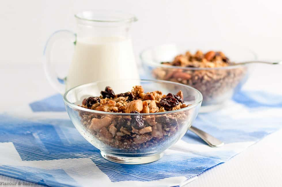 Two bowls of granola with a pitcher of milk