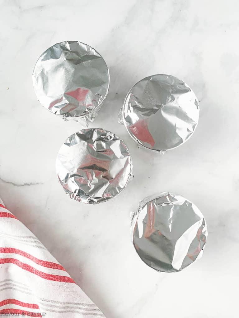 Four ramekins covered in foil