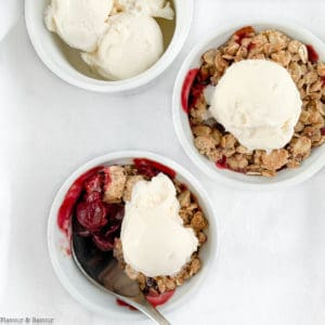 Two ramekins with Cherry Almond Crisp with a dish of ice cream