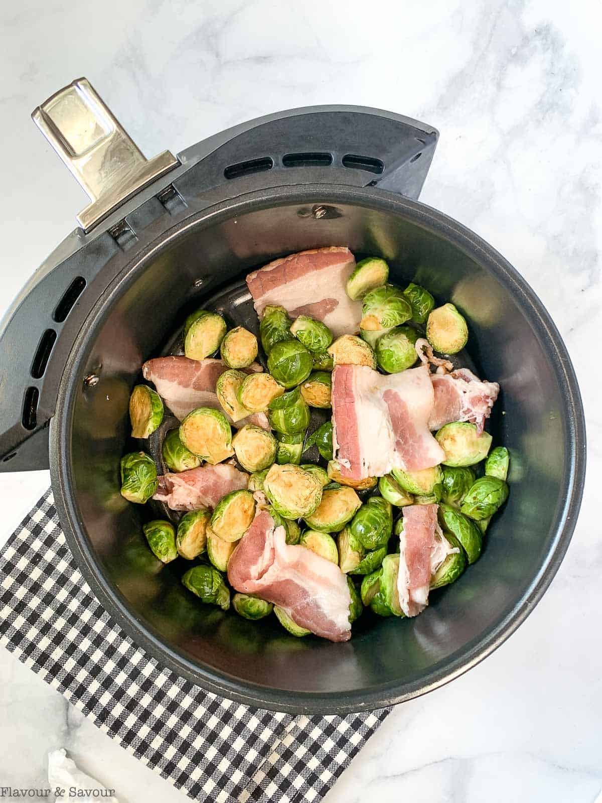 Brussesls sprouts with bacon in air fryer basket before frying