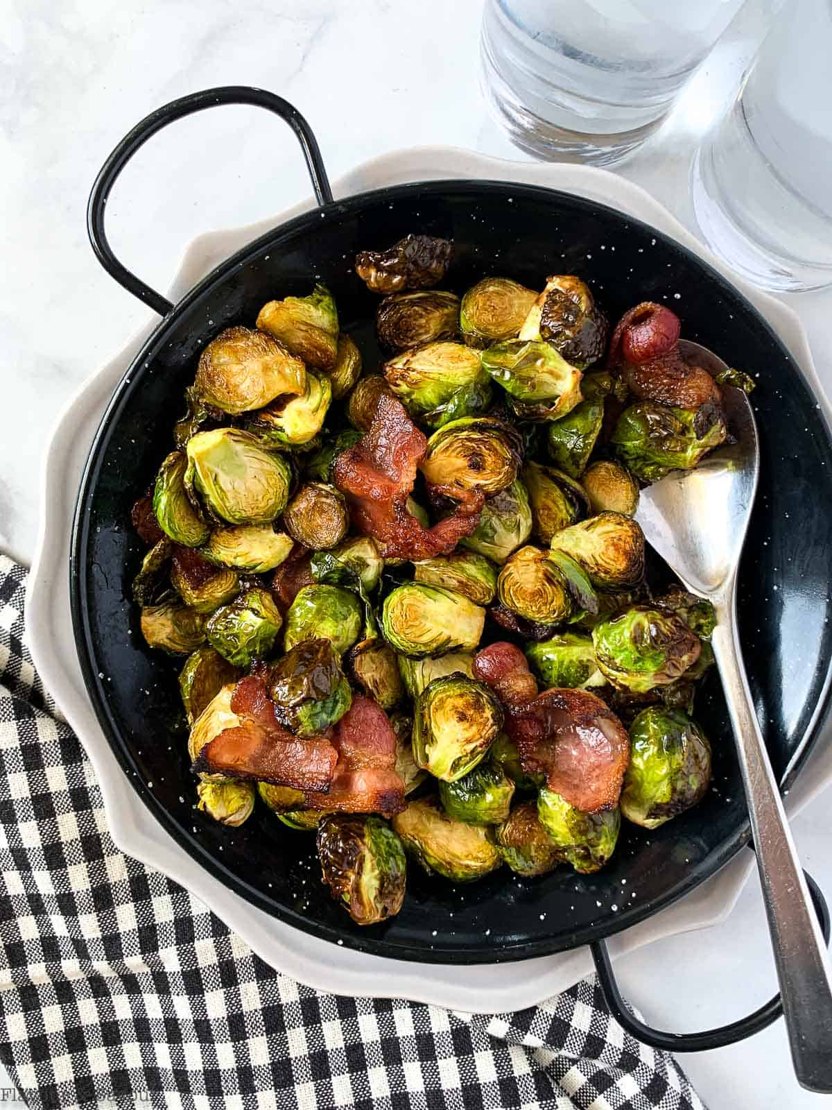 Overhead view of Balsamic Brussels Sprouts with bacon pieces in a black serving dish