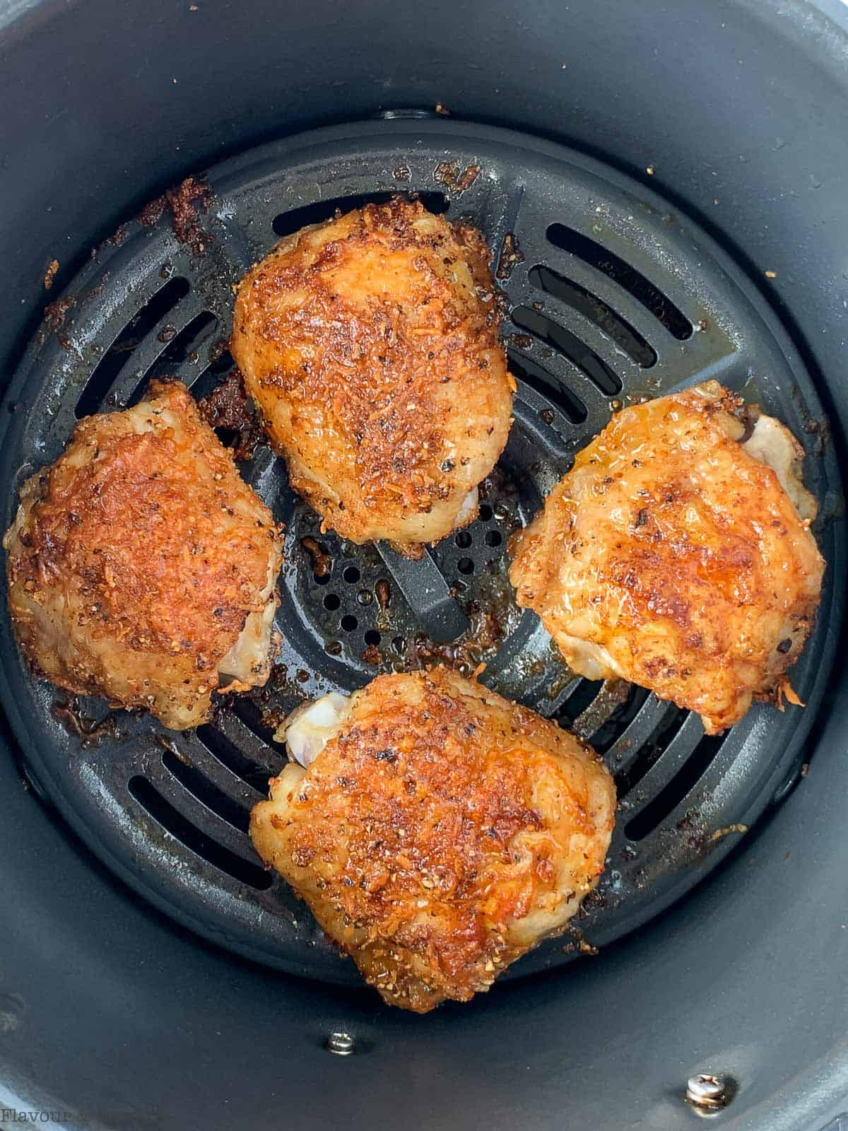 Four cooked chicken thighs in air fryer basket